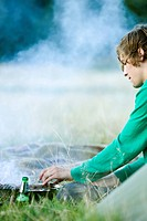A young man having a barbecue (thumbnail)
