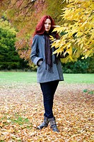 A young woman standing next to a tree in autumn time (thumbnail)