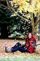 A young woman sitting beneath a tree in autumn time