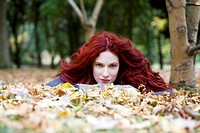 A young woman lying amongst autumn leaves
