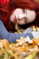 A portrait of a young woman lying on autumn leaves