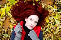 A young woman lying on autumn leaves