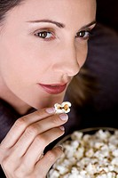 Close_up of a mid adult woman eating popcorn