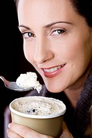 A mid adult woman eating ice cream, close_up