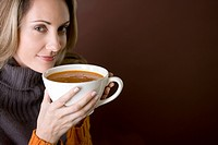 A mid adult woman holding a cup of soup