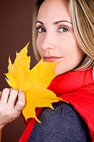 A mid adult woman holding an autumn leaf (thumbnail)