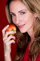 A mid adult woman eating an apple