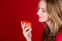 A mid adult woman holding an apple