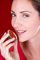 A mid adult woman eating a fig (thumbnail)