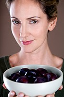 A mid adult woman holding a bowl of plums (thumbnail)