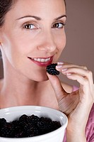 A mid adult woman eating a blackberry