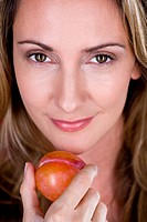 A mid adult woman holding a plum, close_up