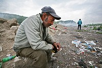 poor roma people trying to make a living by collecting garbage from a disposal-site  they collect empty plastic bottles and make 2 euro per pay for re...