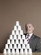Businessman sitting by pyramid of plastic cups