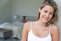 Couple in bedroom focus on smiling woman in foreground portrait