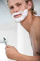 Man shaving face in bathroom portrait