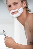 Man shaving face in bathroom portrait