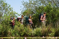 Four teenage boys and girls 16_17 years walking by lake carrying backpack boy reading map