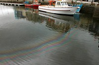 Oil on water in coastal town harbour, Sutton Wharf, Sidmouth, Devon, England, august