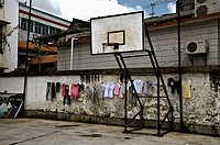 Basketball court with clothes hanging. China