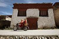 Two monks Lama ride a motobike in the monastery
