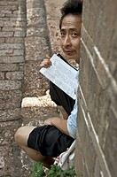 a man reads, sitting in the street. China