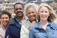 Four senior adults stand in a row smiling at camera