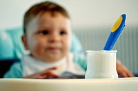 Baby boy in high chair with jar of yogurt and spoon