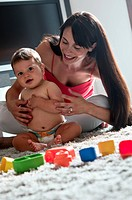 Young woman and baby boy sitting on rug playing with toys