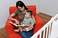 Young woman and baby boy sitting on arm chair reading a book