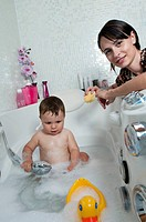 Baby boy taking bath in tub, young woman with sponge