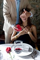 Young man giving a present to young woman with hand covering her eyes