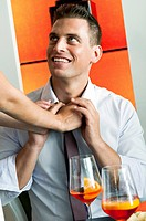 Young woman's arms adjusting young man's tie (thumbnail)