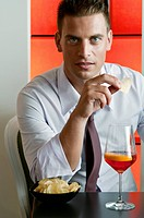 Young man sitting with a glass of orange wine and potato chips (thumbnail)