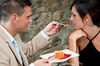 Young man feeding young woman at restaurant
