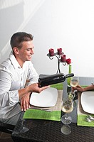 Young man pouring wine for young woman at restaurant table