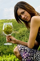 Young woman in vineyard with a wineglass of white grapes (thumbnail)