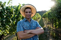 Young man in casual dress in front of vineyard