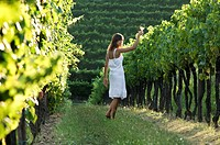 Young woman in vineyard holding wine glass (thumbnail)
