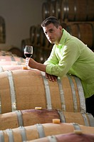 Young man in wine cellar with glass of red wine
