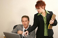 Businessman and his secretary looking at a laptop