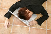 High angle view of a businesswoman sleeping with her head resting on a laptop