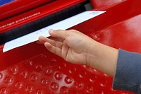 Close_up of a woman's hand dropping mail into a mail slot
