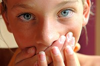 Close_up of a girl covering her mouth with her hands
