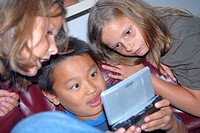 Boy playing a handheld video game with two girls leaning beside him