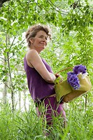 Woman in mid_50's with basket of flowers in grove of trees, Manitoba Canada