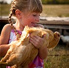 Five year old girl holding heritage breed of free range chicken, Redvers, Saskatchewan, Canada