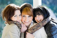 Three happy girlfriends close together with just one scarf