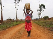 A girl carries a jerrycan down the road  Feeding centres and other humanitarian aid were organised in Angola after widescale malnutrition during and f...
