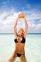 tropical beach: beautiful girl drinking from a coconut in her hands